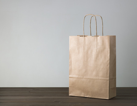 paper bag: disposable bag of kraft paper on a wooden table Stock Photo