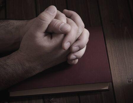 mani incrociate: cravatta palme con le dita incrociate primo piano sulla Bibbia durante la preghiera Archivio Fotografico