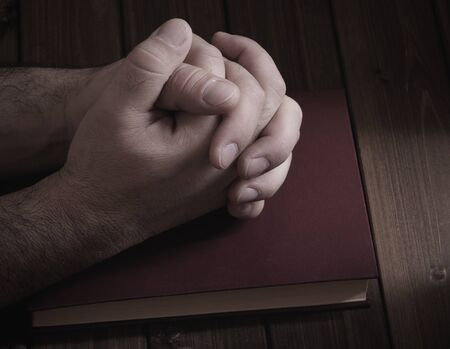 worship hands: tie palms with cross fingers closeup on the Bible during prayer