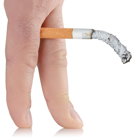potency: smoked cigarette in the fingers of the concept of causing impotence Smoking Stock Photo