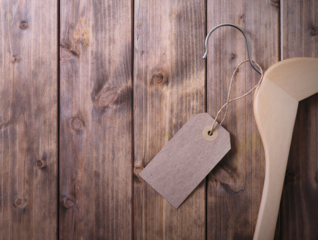 coat hanger with blank tag on background of wooden planks Stock Photo