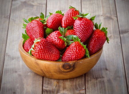 a bunch of ripe strawberries in a wooden bowl on the table Stock Photo