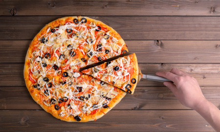 Pizza with cheese and pizza paddle on wooden table background