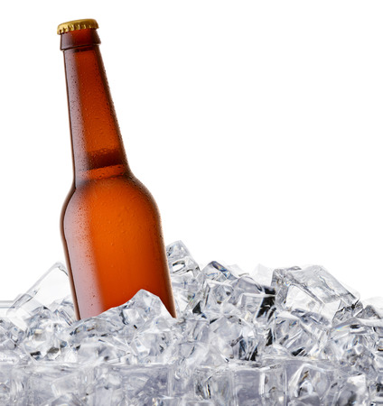 beer bottle getting cool in ice cubes. Isolated on a white background. Stock Photo