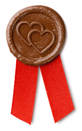 brown wax seal with hearts and ribbon isolated on white with clipping paths Stock Photo