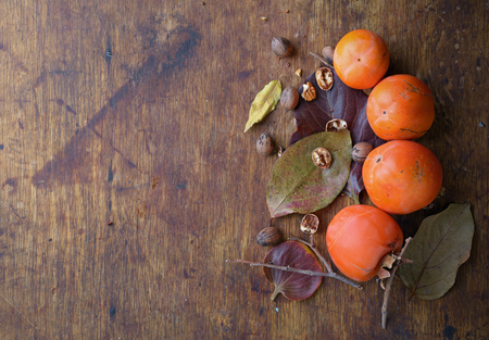 harvest: ripe persimmon with pecans on the old wooden background