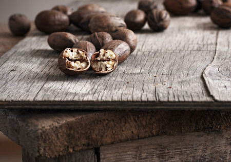 whole pecans: whole and chopped pecan nuts on old wooden table.