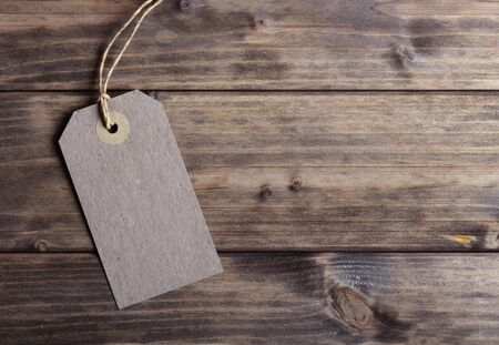 Blank price tag on the background of wooden planks