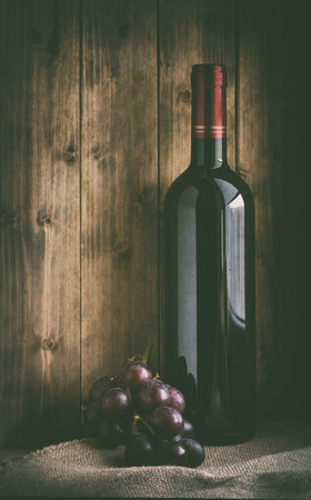 art processing: bottle of red wine with grapes on sacking and wooden background in retro style