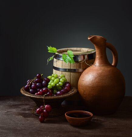 stillevens en beker wijn met een kruik, een houten vat en druiven in een kom