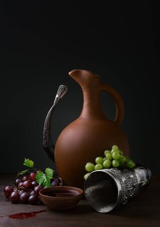 cup of wine pitcher drinking horn and grapes on a wooden table Stock Photo