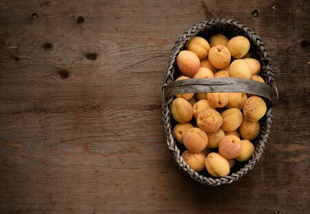 Full basket with ripe apricots on a wooden table