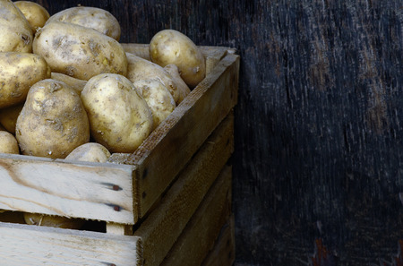 Fresh potatoes in a wooden box on a dark background Stock Photo
