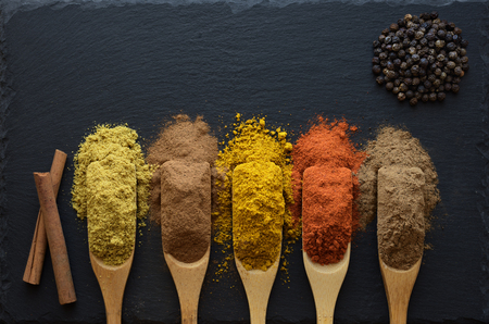 colorful herbs and spices in wooden spoons on black stone background,  top view.