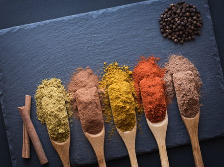 colorful herbs and spices in wooden spoons on black stone background,  top view. Stock Photo