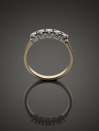 Gold ring with brilliants on dark background