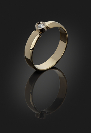 gold ring with a diamond on a dark background is cut with clipping paths