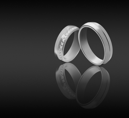 couple wedding engagement rings on dark background