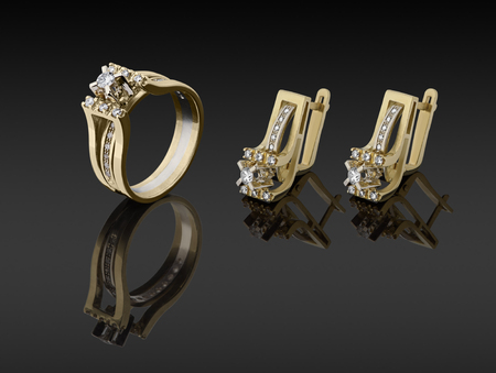 gold ring and earrings with diamonds on dark background