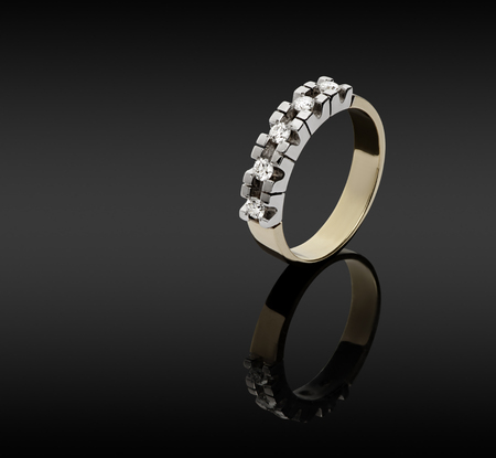 Female gold ring with diamonds on a dark background