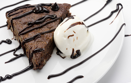 slice of cake brownie with ice cream on white plate