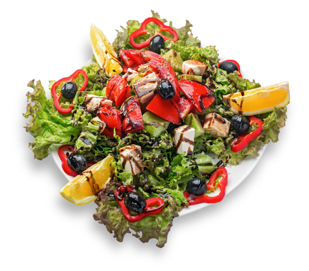 Fresh Greek salad on a plate isolated on white background.