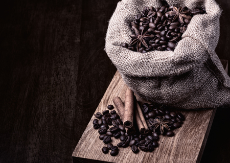 bag of black coffee beans on wooden background