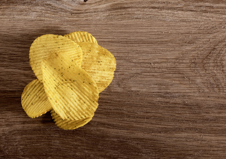 corrugated potato chips on wooden background