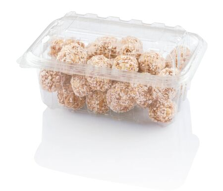 rounds candy with coconut shavings in a plastic container isolated on white with clipping paths