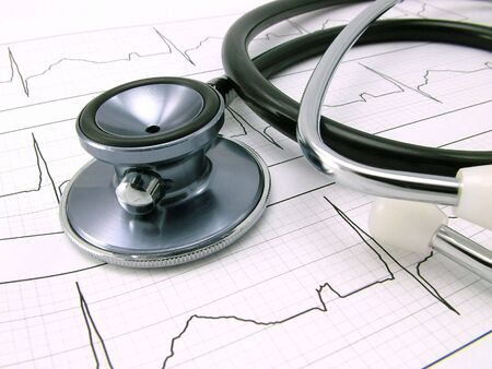 A stethoscope on an Electrocardiogram - ECG. ECG graph is the standard 12-lead.