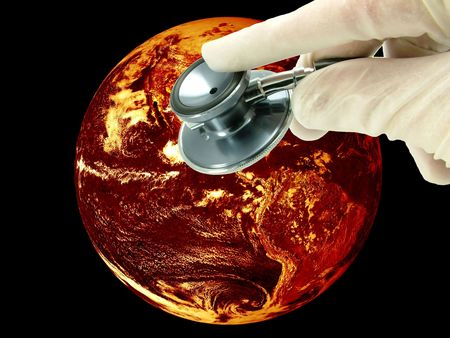 Global warming climate change concept. A health check of planet earth. The world is overheating due to climate change and shown in a fiery red and orange volcanic glow, with the hand of a Doctor and stethoscope.