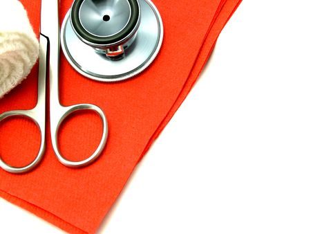 Doctors stethoscope, cutting scissors, medical tools and bandage on red paper, over white background.