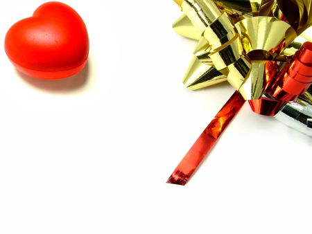 A glowing red valentine love heart with shiny gold bow and red ribbon over white background.