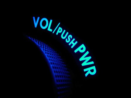 Cyan and blue neon lights glow in a dark blue haze on a power and volume handle.