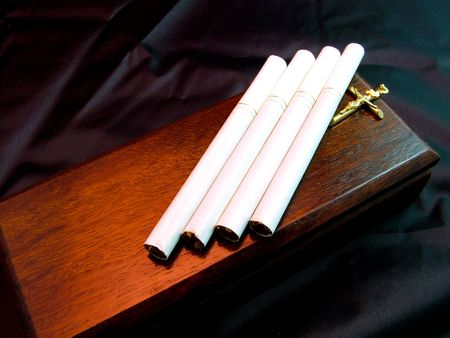 Four menthol cigarettes on a timber coffin with gold cross and black texture background. Health concept signifying death due to smoking.