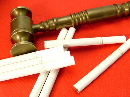 proceedings: A brass judges gavel with a number of cigarettes. Concept of smoking litigation and court proceedings. Stock Photo