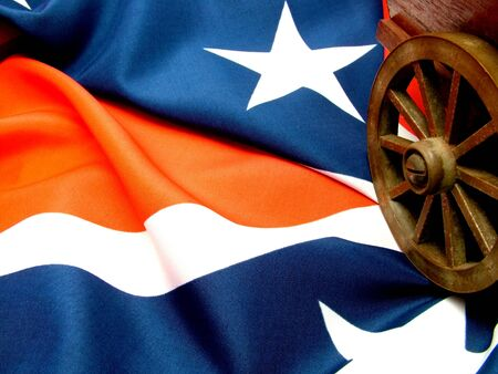 An old cart and cartwheel on a United States of America confederate flag.