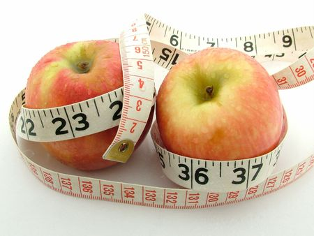 Two red apples with a black and red weight watching measuring tape. Stock Photo