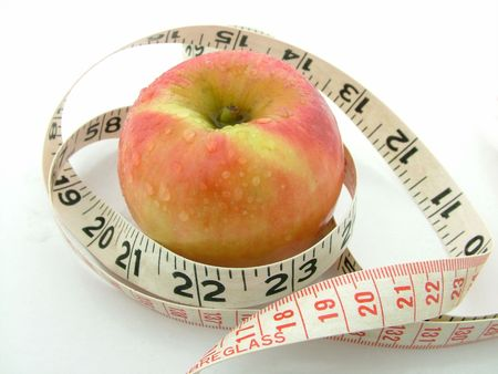 A red apple with a black and red weight watching measuring tape. Stock Photo - 890568