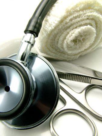 tijeras cortando: Un estetoscopio de los doctores, una tijera que corta, herramientas m�dicas y un fondo del blanco del excedente del vendaje Foto de archivo