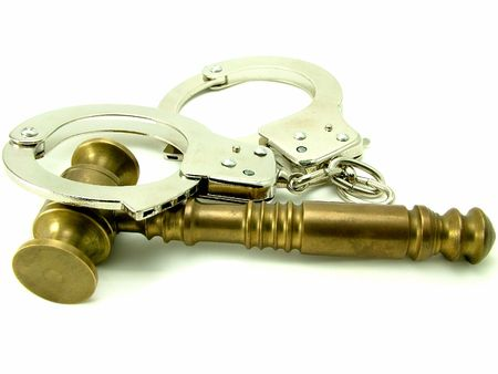A brass judges gavel and hand cuffs over white background photo
