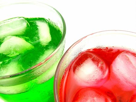 Red and green flavored icy cold drinks with ice blocks on white background.
