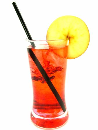 Red swirls of flavor in a cold and icy orange flavored iced drink with straw and apple slice.
