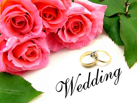 A pink bunch of roses with green rose leaves, wedding wording and wedding and engagement rings over white background.