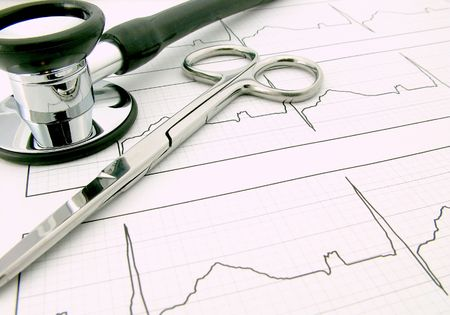 A Doctor stethoscope and pair of scissors on a white Electrocardiogram - ECG. ECG EKG graph is the standard medical 12-lead.