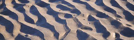 Seaside beach sand at sunset with wind rippled ridges