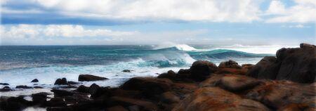 Wild surfing scene with wind-driven sea spray near a coastline