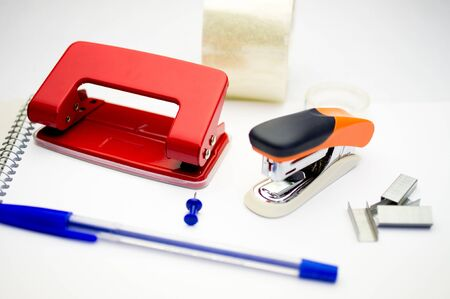 office stapler: Hole punch, stapler, pen, tape, paper clips, bright colors on the notebook