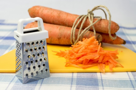 conjunction: Grated carrot, grater for vegetables, carrot farm in conjunction Stock Photo