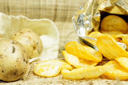 Natural potato chips in a package and potatoes in the bag photo